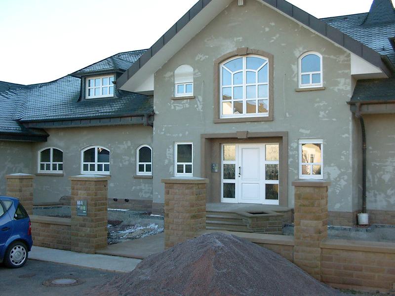 Neubaugestaltung, Fenster- und Türgewände sowie Mauer, Pfeiler und Abdeckung in Kylltaler Sandstein gebaendert und rot.JPG